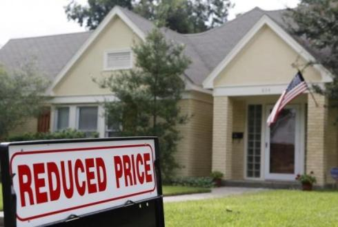 An advertisement for a reduced price is seen outside of a home for sale in Dallas